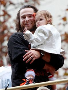 San Francisco Giant Brandon Crawford cradles his daughter Braylyn during the start of the World Series victory parade Friday, Oct. 31, 2014, in San Francisco, Calif. (Karl Mondon/Bay Area News Group)
