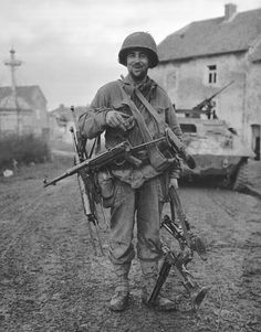 A GI with captured weapons, Battle of the Bulge, 1944.
