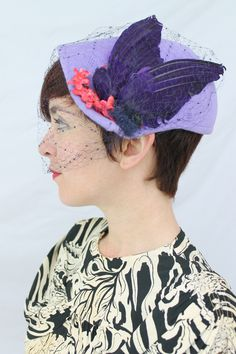 1950s-style cocktail hat (blocked on a fifties era hat block) - lavender fur felt, vintage fancy navy blue veiling, red vintage flowers, and a vintage purple double faux bird. A purple velvet ribbon along the interior of the hat creates visual interest.