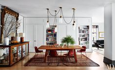 love the combo of rustic chairs, warm wood table, antique mirror, fabulous modern lighting, and glass sideboard for display
