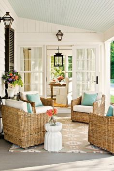 Warm wicker, ivory cushions, pale blue accent pillow, beige/ivory rug, and a side table with potted flowers.
