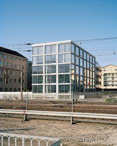 Ein strenges, orthogonales Raster prägt die Fassade, am Tag reflektieren die Gläser die umgebenden Gebäude