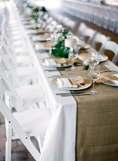 Long tables set with white linens and burlap runner.  White wood folding chairs (every other chair with a red detail or sash, knotted)