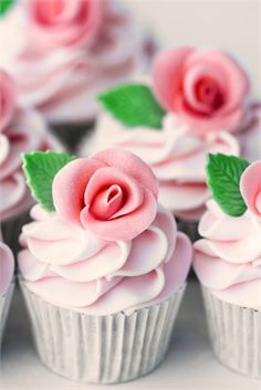 Cupcakes with pink icing and sugar rose decorations