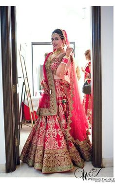 Desi bride in a red and gold Indian bridal lehenga.