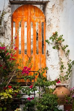 Love the peeling stucco and arched door, the flowers bring it to life again~❥
