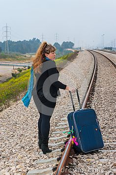 Young woman with a suitcase on the railroad