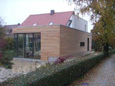 Ein Massivholzanbau mit Flachdach erweitert die Wohnfläche des Siedlungshäuschens.