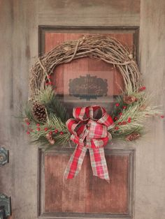 Beautiful grapevine wreath with pine branches, red berries and pine cones