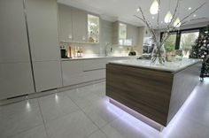 Two tone kitchen arrangement designed to make a feature of the kitchen island.  Smooth cashmere gloss lacquer base and wall units are the ideal backdrop for a stunning grey acacia laminate floating kitchen island. #kitchenisland #kitchen #lwkkitchens