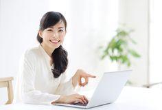 ノートパソコンを指差す若い女性