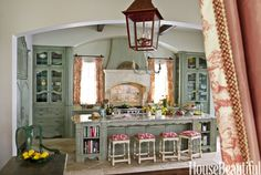 """To create beautiful green cabinets for this French-inspired Texas kitchen, designer Michele Allman used an unusual technique. """"We started with Benjamin Moore's November Rain and then added layer upon layer of pigment and glaze to build up this crusty finish,"""" she says. The Minton-Spidell stools are covered in Brunschwig & Fils' La Mer in Pompeian Red. Pavia Antico walnut travertine on floor from Walker Zanger."""