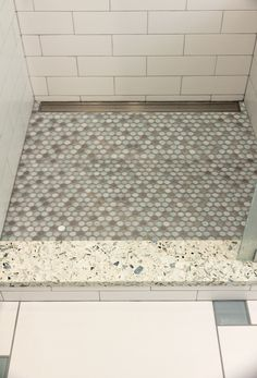 Shower threshold in vetrazzo, penny mosaic tile shower floor with trough style drain, subway tile walls and large white tile with square glass accents on the floor