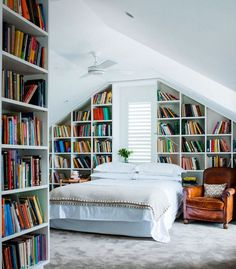 I love everything about this room - the white bedding, the worn leather chair, the eaves, and especially the bookshelves!