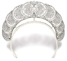 Belle Epoque DIAMOND TIARA, 1920s.    Designed as a graduated series of open work plaques of palmette, acanthus leaf and floral cluster motifs, pierced and millegrain-set with circular-, single-cut and rose diamonds; detachable, most probably the tiara was designed to be worn also as a collier de chien