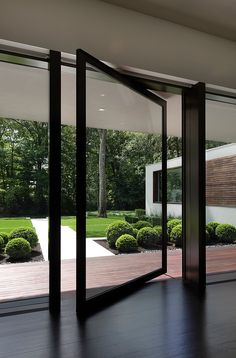 Window to a garden scattered with box hedges | adamchristopherdesign.co.uk