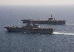 The Wasp-class amphibious assault ship USS Essex (LHD 2) transits alongside the aircraft carrier USS Theodore Roosevelt (CVN 71).