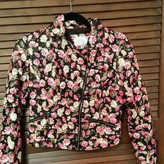 Multicolor flower moto  jacket NEVER WORN This jacket would be so cute with a black dress or jeans. It is a leathery  material and has zip pockets. It is in perfect condition, never worn. Xhilaration Jackets & Coats