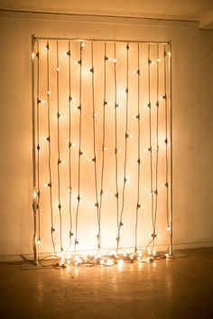Wedding ceremony backdrop idea...one or two strands of patio lights strung up and down this makeshift metal frame.
