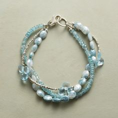 ICE STORM BRACELET -- Sterling silver beads, blue zircon, topaz and mystic sapphire in this bracelet. Three strands, lobster clasp.