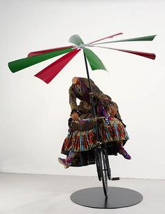'Woman on Flying Machine' (2008) by London-based, British-Nigerian artist Yinka Shonibare, MBE (b.1962). Mannequin, Dutch wax printed cotton, steel, rubber & aluminum.  Mannequin: Approx. 53.1 x 39.4 x 31.5 in, Flying Machine: 78.7 x 23.6 x 35.4 in. via James Cohan Gallery