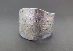 Starry Night Cuff An oxidized sterling silver cuff bracelet with 22k yellow gold, 24k yellow gold and 3.63 total carat weight of sapphires, tourmalines and garnets. Designed and made by llyn strong.
