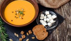 Pumpkin soup with bread crouton on the dark wooden table.