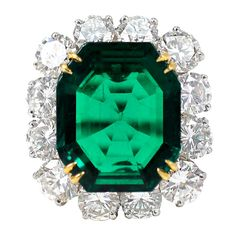 Emerald cut cornered aschers cut with hexagon cut white diamonds on yellow gold. Very rare cut for an emerald, nice color!