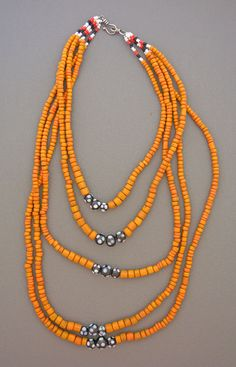 Five descending strands of orange glass beads from Indonesia  with white, red, black, and polka dot beads. The sterling silver  hook and eye clasp was handmade in Sri Lanka.