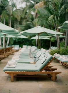 Mint green pool loungers and umbrellas