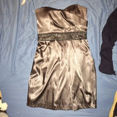 Strapless, grey, silky, semi formal dress. Silky, strapless, grey/silver (little darker then shown in picture). Beaded midline strip. Has pockets Taboo Dresses Strapless