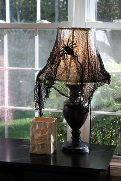Halloween Lamp Idea. Black netting, Fishnet Stocking cut up , or  Cheesecloth dyed black. Just place over  lamp and add spiders, snakes, bugs.. Your choice.