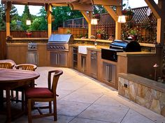 I like this L-shaped outdoor kitchen, particularly with the narrow arbor running over the counter.  I think I could adapt this style to my kitchen site, which has architectural issues with a bay window and nearby covered patio.