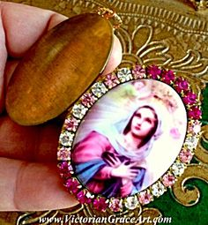 $77 Vintage Virgin Mary Ex-voto Rhinestone Cameo Locket Pendant (Image1) Religious Jewelry: Pendant / Locket - Large porcelain cameo featuring The Blessed Mother Virgin Mary with a small Angel lowering a crown onto Mary's head. Fuschia, pink and clear rhinestones surround. Inside this vintage locket is brass and copper and can hold 2 photo's and/or a prayer petition request to Mary.
