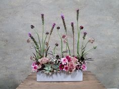 Marble echeveria succulents, roses, ranunculus, mums, astrontia and liatris create a meadowy effec