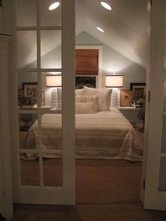 Interesting idea... create a wall-length cabinet (shelf behind/above headboard to bring bed out from under steeper part of eaves while also providing storage. Use french doors to increase light flow in tight space. Nice.