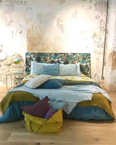 Le lin uni réchauffe cette chambre dans un loft au mur en béton brut