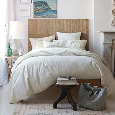 white bedroom with texture in headboard, dhurrie rug, smooth glass, chenille