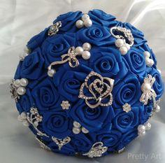 """Buquê de flores azul royal em cetim com broches prateados e pérolas. <br> <br>Os buquês são personalizados e montados de acordo com o gosto da noiva. <br> <br>Eles são únicos sendo que nunca existirá um buque idêntico ao outro. <br>Composto de broches em tons de prata cravejados em strass, flores de cetim e pérolas. <br> <br>Possui 19cm diâmetro <br> <br>A escolha do buquê de noiva é tão importante quanto a escolha do vestido. <br>O """"Bouquet de Broches"""" é uma verdadeira semi jóia <br…"""