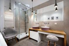 Szarość tej łazienki przełamano drewnianym blatem i subtelnym kolorem emaliowanych umywalek. W tafli dużego lustra ukryto dyskretnie niewielkie schowki. Vinatge'owy fotel wnosi do wnętrza salonowy styl.