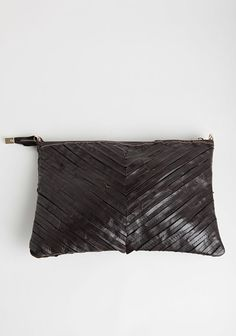 Dark brown oversized leather clutch featuring strips of sewn leather forming a chevron design.