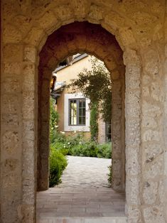 The entrance to this courtyard is bold, with double stone archways attached with a short hallway. The combination of rustic stone and natural beauty give it the feel of an aged cottage garden.