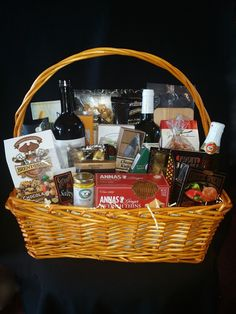 Over The Top Gift Basket in rectangular basket: 2 bottles of wine, sparkling cider, olives, nuts, cheese, crackers, cookies and many more gourmet treats.