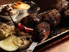 GRILLED LAMB KAFTA `KHASHKHASH´. Grilled kebab skewer of minced lamb, spicy tomato sauce, fennel salad, sesame hummus, harissa.