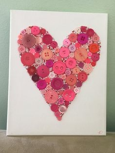 Beautiful heart shape on a white canvas. The heart is made using a variety of red and pink plastic buttons, various shades of red and pink glass beads, and clear plastic rhinestones.