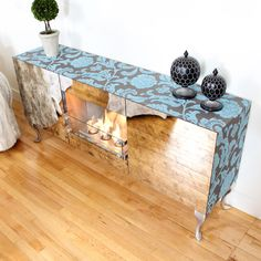 Mirror Console Fireplace. Burns 3 to 5 hrs using three disposable gel fuel cells and requires no ventilation.