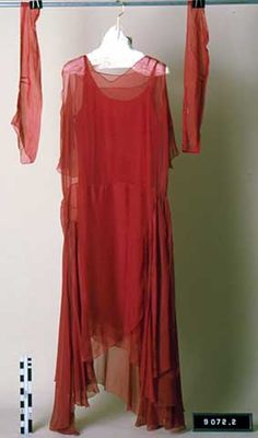 Floor length melon red chiffon sleeveless chemise evening gown has V-neck front, back capelet attached at neckline, layers of chiffon attached at waist, and uneven hem. Crepe underdress (slip). Melon red chiffon long sleeves, detached. c1925-29