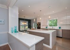 Contemporary open concept kitchen with white cabinets, quartzite countertops, white backsplash, stainless appliances, medium tone hardwood floors, an island, an undermount sink and flat-panel cabinets.