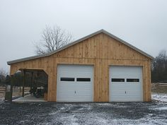 This Pole Barn has wide lean-to, two overhead garage doors, one entry door under the overhang, metal roofing and wo. Pole Barn Garage, Building A Pole Barn, Post Frame Building, Building A Garage, Carport Garage, Pole Barn House Plans, Pole Barn Homes, Garage House, Pole Barns