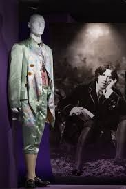 FIT. 1750's. The suit is silk and embellished and colorful. Oscar Wilde is in the background.